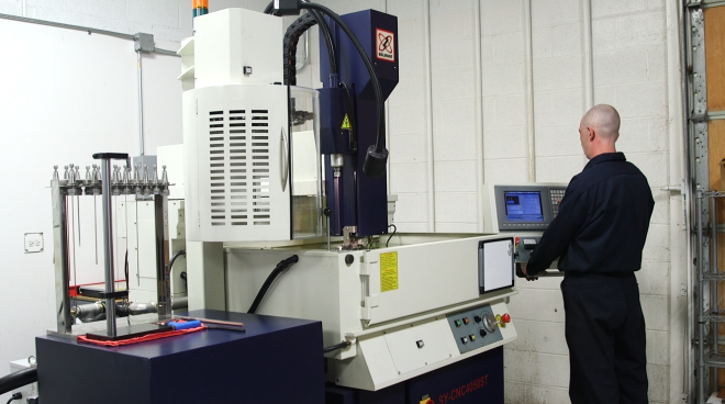 technician using EDM drill to create coolant holes in tooling