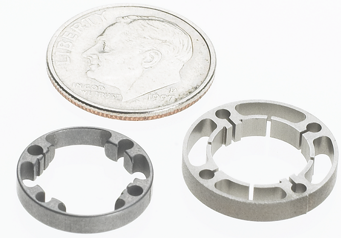 machined metal endo rings next to a dime for scale